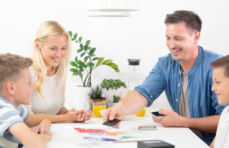 Het gelukkige jonge spel van de familiespeelkaart bij eettafel bij helder modern huis stock fotografie