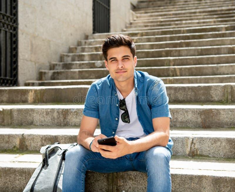 Het gelukkige jonge student mannelijke texting op zijn slimme telefoon in modern ci stock afbeelding