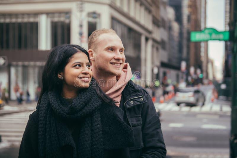 Het gelukkige jonge volwassen paar kijkt aan de partij die zich op de Stadsstraat van New York verenigen royalty-vrije stock afbeelding