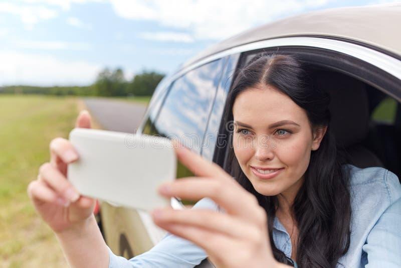 Het gelukkige jonge vrouw drijven in auto met smartphone royalty-vrije stock foto's