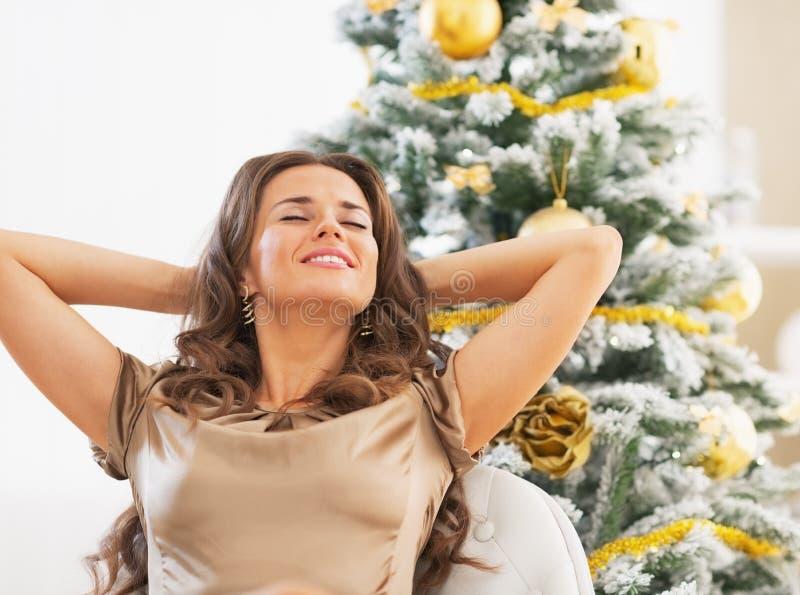 Het gelukkige jonge vrouw ontspannen voor Kerstmisboom stock fotografie