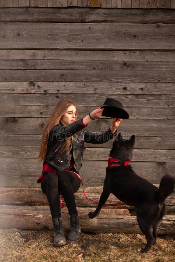 Het gelukkige jonge vrouw plaing met haar zwarte hond in fron van oud blokhuis Het meisje probeert een hoed aan haar hond royalty-vrije stock afbeeldingen