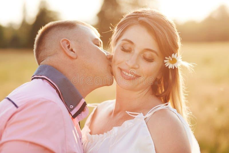 Het gelukkige jonge wijfje ontvangt kus van vriend, heeft openluchtgang over gebied, toont liefde aan elkaar Het mooie paar stelt stock foto's