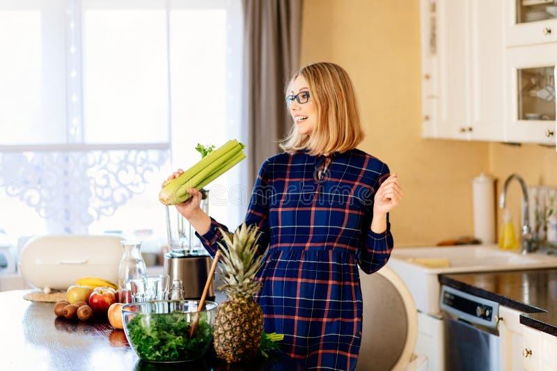 Het gelukkige jonge zwangere vrouw zingen met selderie in keuken stock afbeelding