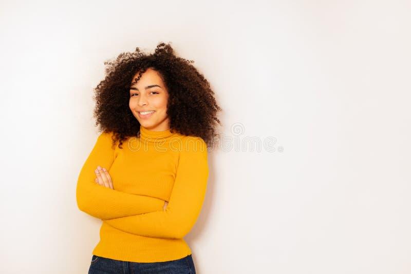 Het gelukkige jonge zwarte meisje van de studentenleeftijd met krullend haar stock fotografie