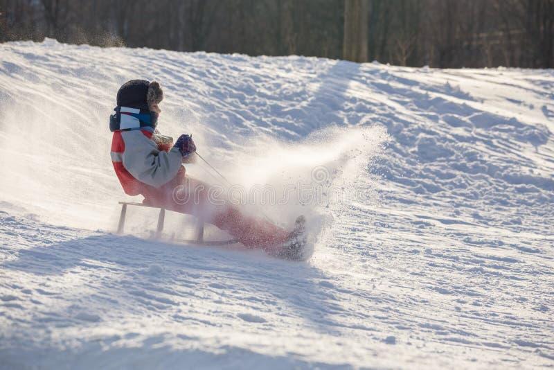 Het gelukkige jongen berijden bij de dia op sneeuwheuvel stock foto's