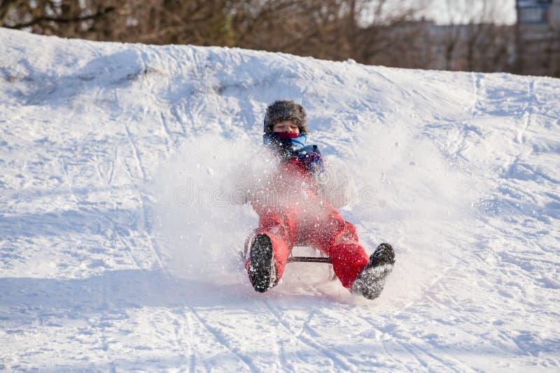 Het gelukkige jongen berijden bij de dia op sneeuwheuvel royalty-vrije stock fotografie