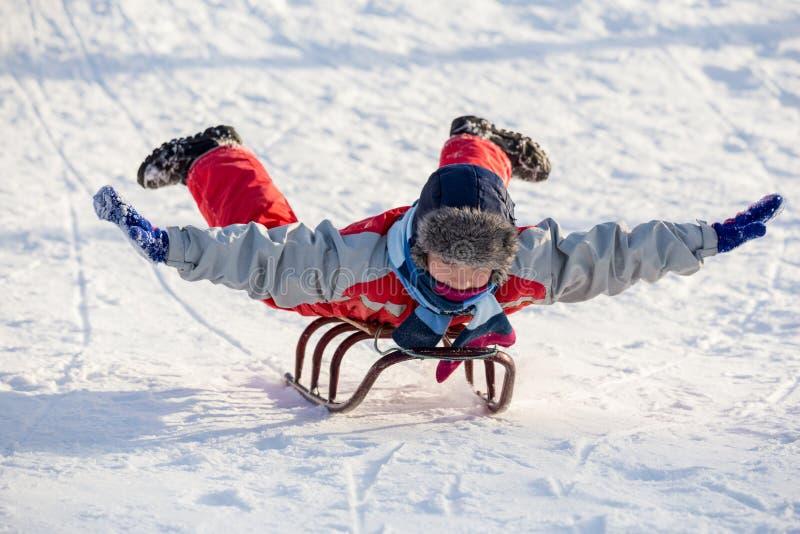Het gelukkige jongen berijden bij de slee op sneeuwheuvel stock afbeeldingen
