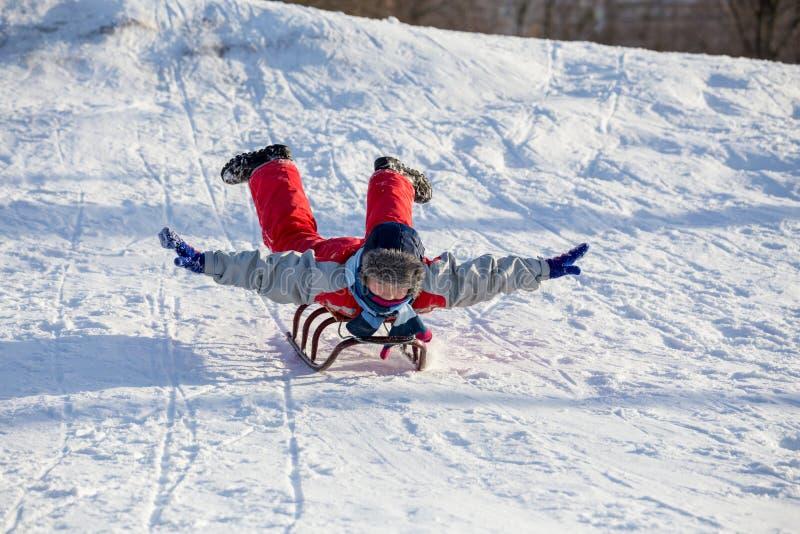 Het gelukkige jongen berijden bij de slee op sneeuwheuvel stock afbeelding