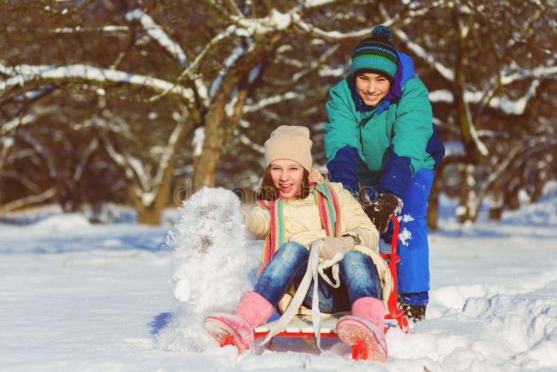 Het gelukkige jongen en meisjes sledding in de winter openlucht royalty-vrije stock fotografie