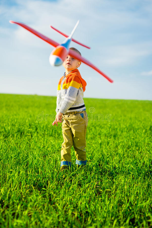Het gelukkige jongen spelen met stuk speelgoed vliegtuig tegen blauwe de zomerhemel en groene gebiedsachtergrond royalty-vrije stock afbeelding