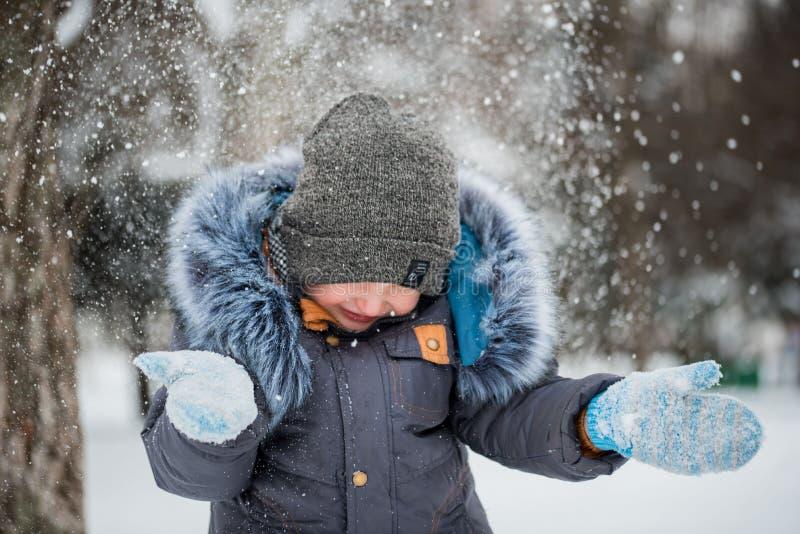 Het gelukkige jongen spelen in sneeuw, de winterspelen royalty-vrije stock afbeelding