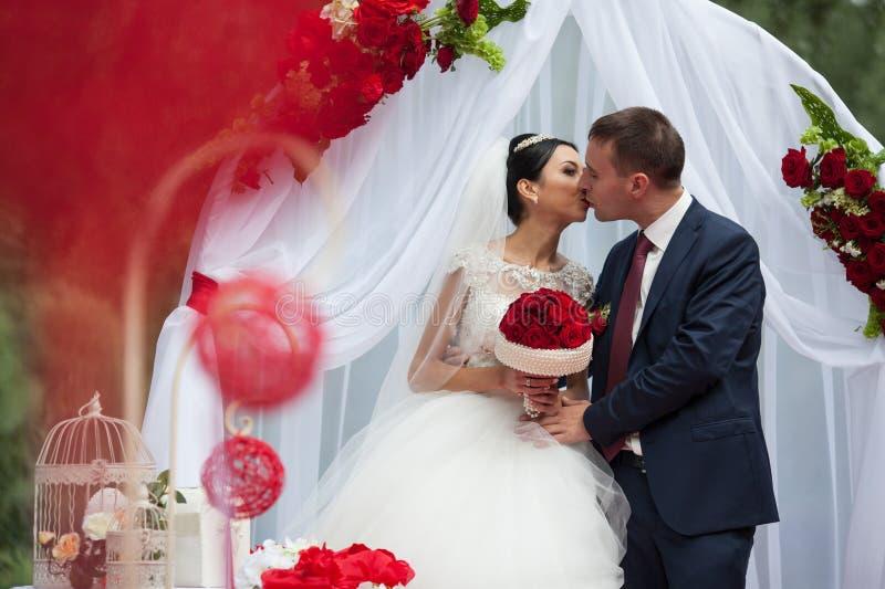 Het gelukkige jonggehuwde romantische paar kussen bij huwelijksdoorgang met rood stock afbeeldingen