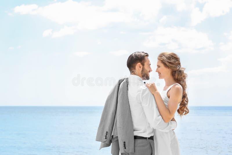 Download Het Gelukkige Jonggehuwdepaar Koesteren Stock Afbeelding - Afbeelding bestaande uit horizon, kaukasisch: 107702401