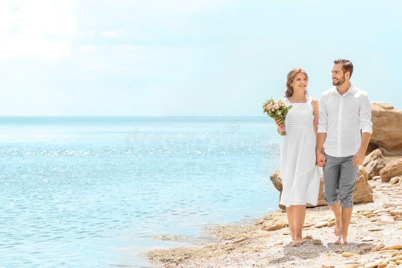 Download Het Gelukkige Jonggehuwdepaar Lopen Stock Foto - Afbeelding bestaande uit bruids, strand: 107702206