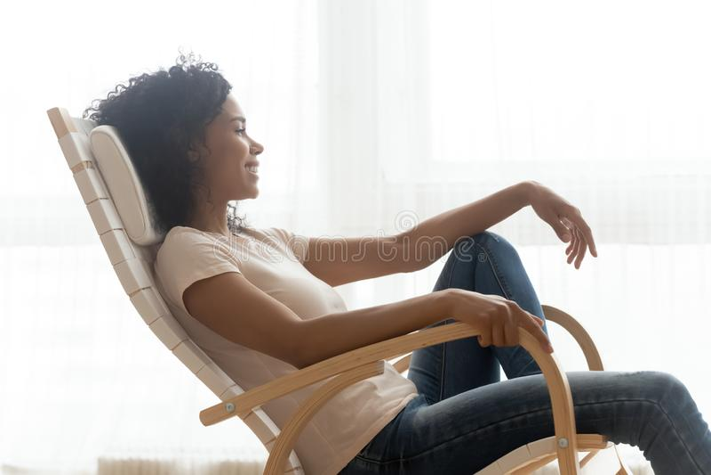 Het gelukkige kalme Afrikaanse meisje rustende dromen zit in schommelstoel royalty-vrije stock fotografie
