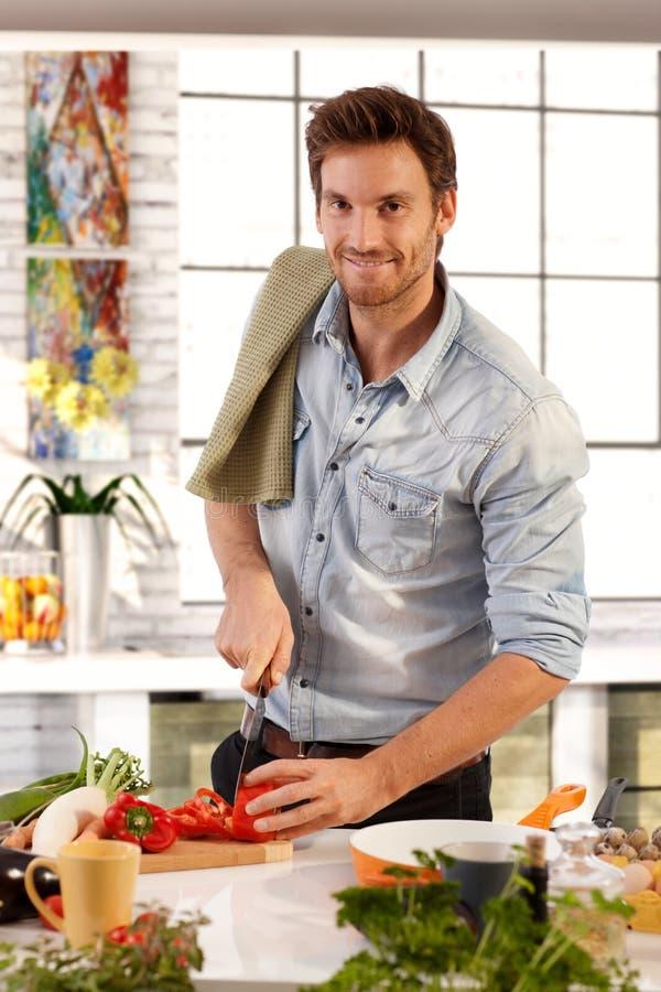 Het gelukkige Kaukasische mens koken in keuken thuis stock foto's