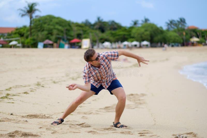 Het gelukkige Kaukasische mens spelen op strand die stenen op oceaan, Bali werpen royalty-vrije stock foto