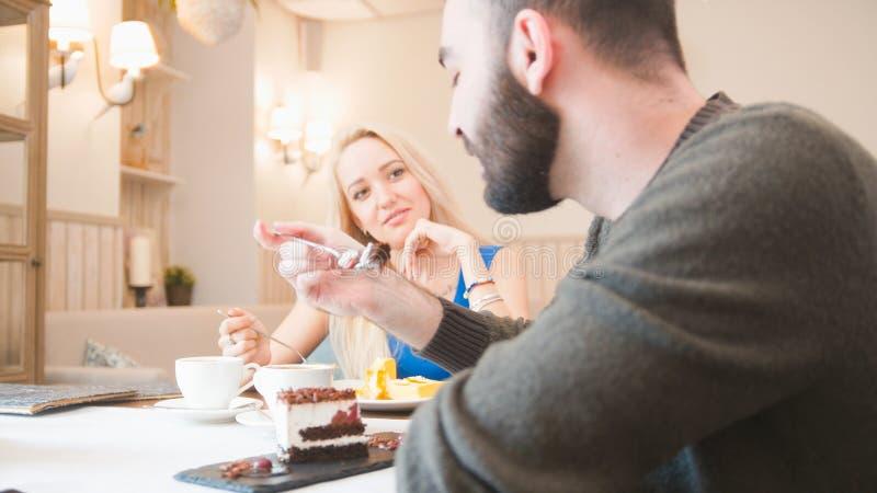 Het gelukkige Kaukasische paar neemt desserts en het spreken bij de koffie royalty-vrije stock afbeeldingen