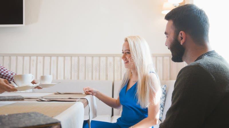 Het gelukkige Kaukasische paar neemt het menu bij de koffie royalty-vrije stock afbeelding