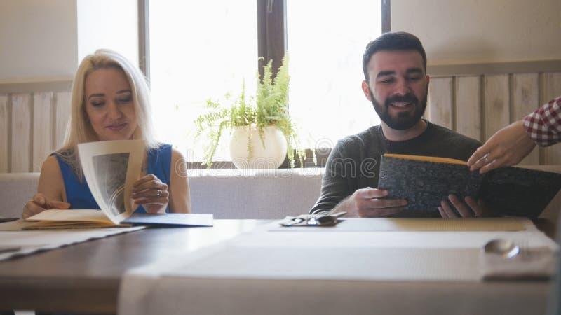 Het gelukkige Kaukasische paar neemt het menu bij de koffie stock foto