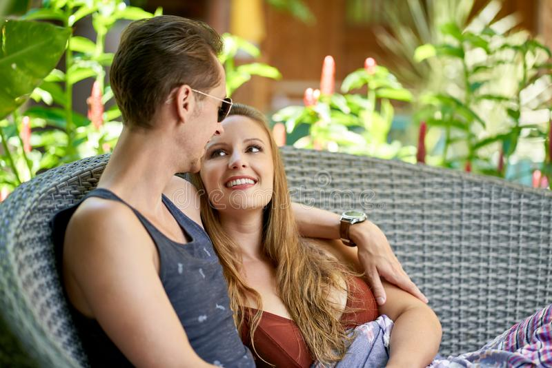 Het gelukkige Kaukasische paar ontspannen in moderne stoel van luxueus die hotel en kuuroord in Bali in tropische bloemen wordt o royalty-vrije stock foto's