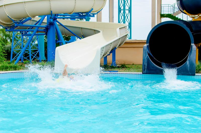 Het gelukkige kind heeft pret op waterdia op openlucht zwembad royalty-vrije stock afbeelding