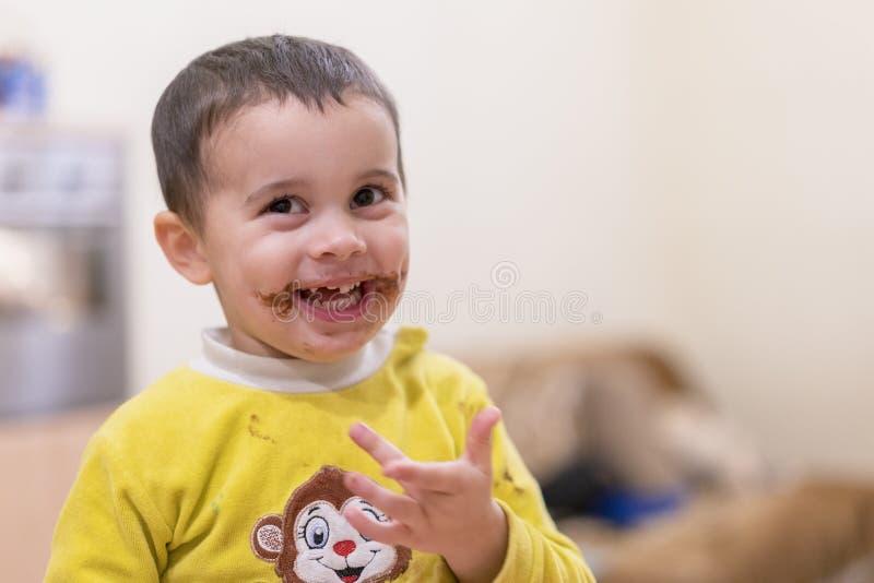 Het gelukkige kind likt een lepel met chocolade Gelukkige jongen die chocoladecake eten Grappige baby die chocolade met een lepel stock afbeelding