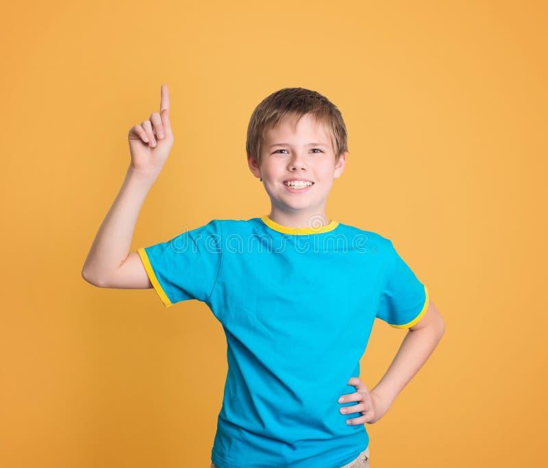 Het gelukkige kind met goed die idee houdt vinger omhoog op gele bedelaars wordt geïsoleerd stock foto's