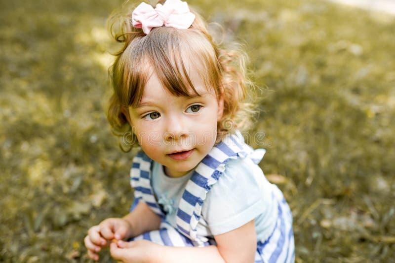 Het gelukkige kind in het park, Jong meisje ontspant in openlucht Kinderjaren royalty-vrije stock fotografie