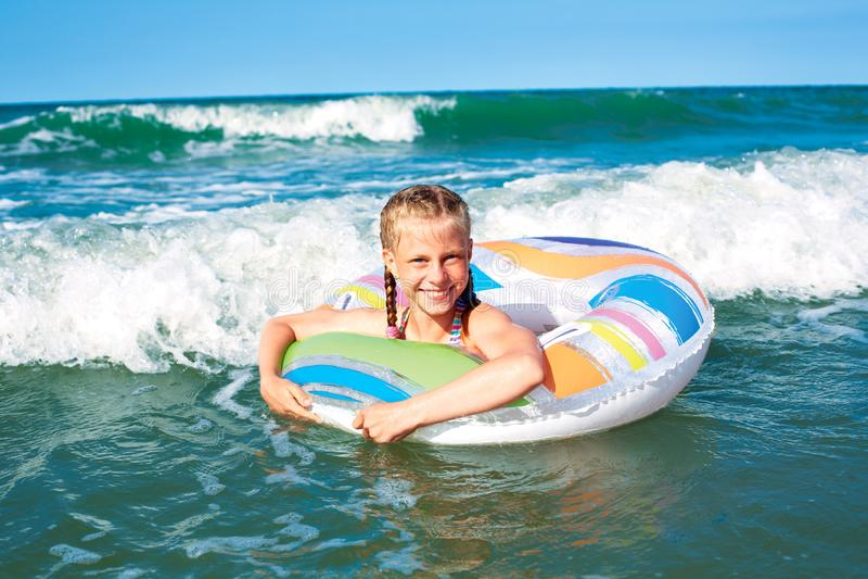 Het gelukkige kind spelen in blauw water van oceaan op een tropische toevlucht bij het overzees Het vrolijke meisje zwemt in de b royalty-vrije stock fotografie