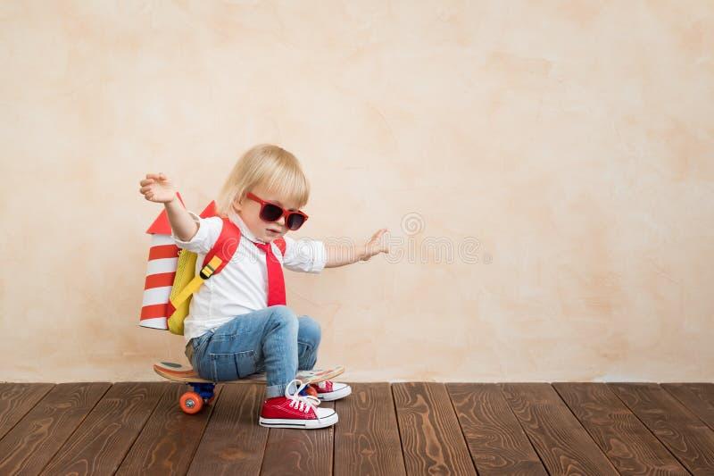 Het gelukkige kind spelen met stuk speelgoed raket thuis stock fotografie