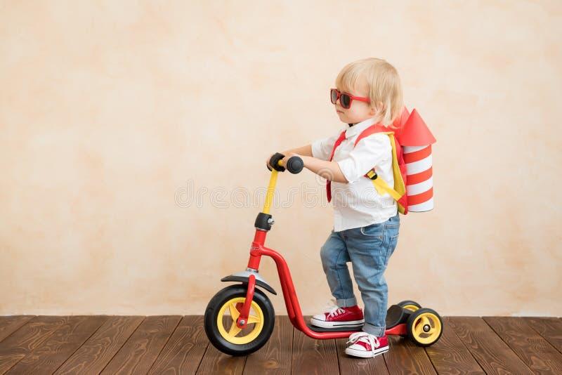 Het gelukkige kind spelen met stuk speelgoed raket thuis stock foto