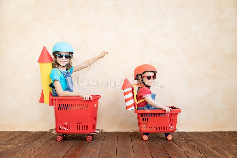 Het gelukkige kind spelen met stuk speelgoed raket thuis stock foto's