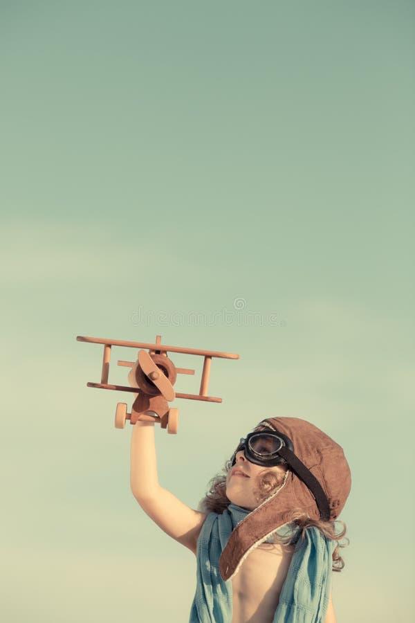 Het gelukkige kind spelen met stuk speelgoed vliegtuig tegen de zomerhemel stock foto