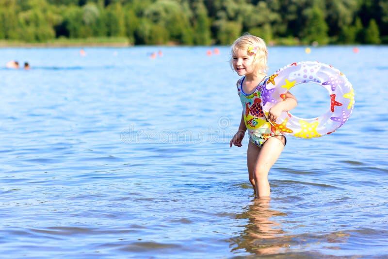 Het gelukkige kind spelen op het strand stock foto's
