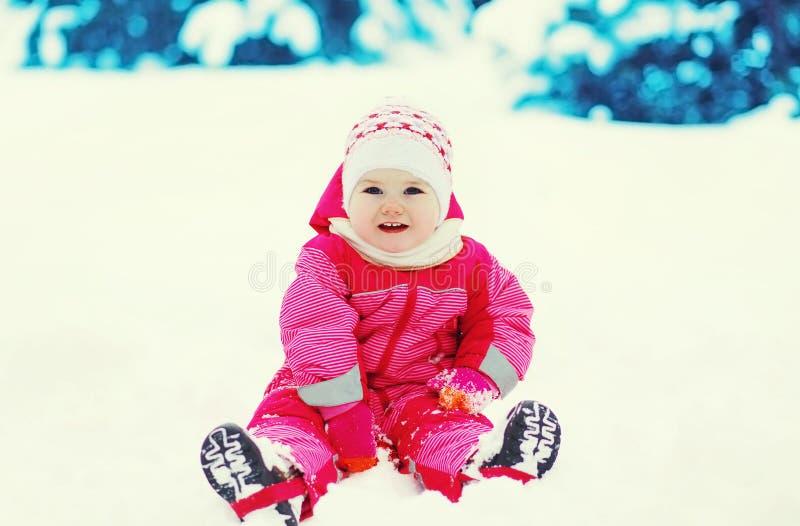 Het gelukkige kind spelen op sneeuw in de winterdag stock fotografie