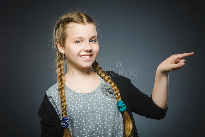 Het gelukkige kind toont op iets Close-upportret van het knappe meisje glimlachen stock afbeeldingen