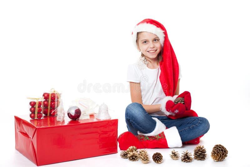 Het gelukkige kind van het meisjesjonge geitje in de sokken van de de hoedengift van santa royalty-vrije stock foto's