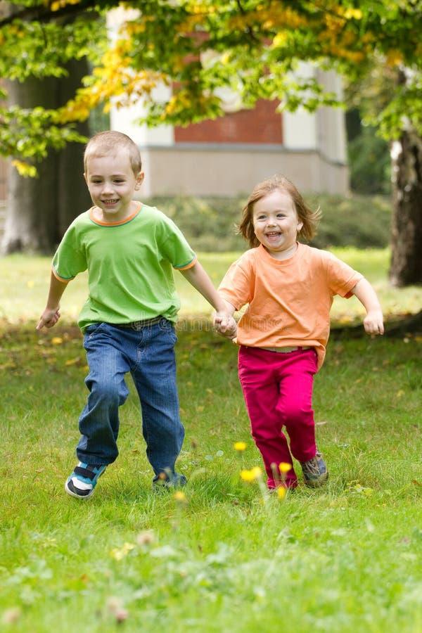 Het gelukkige kinderen lopen stock afbeeldingen