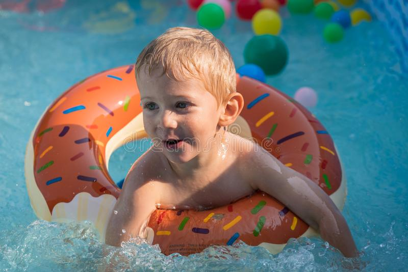 Het gelukkige kindjongen spelen met kleurrijke opblaasbare ring in openlucht zwembad op hete de zomerdag De jonge geitjes leren t royalty-vrije stock foto