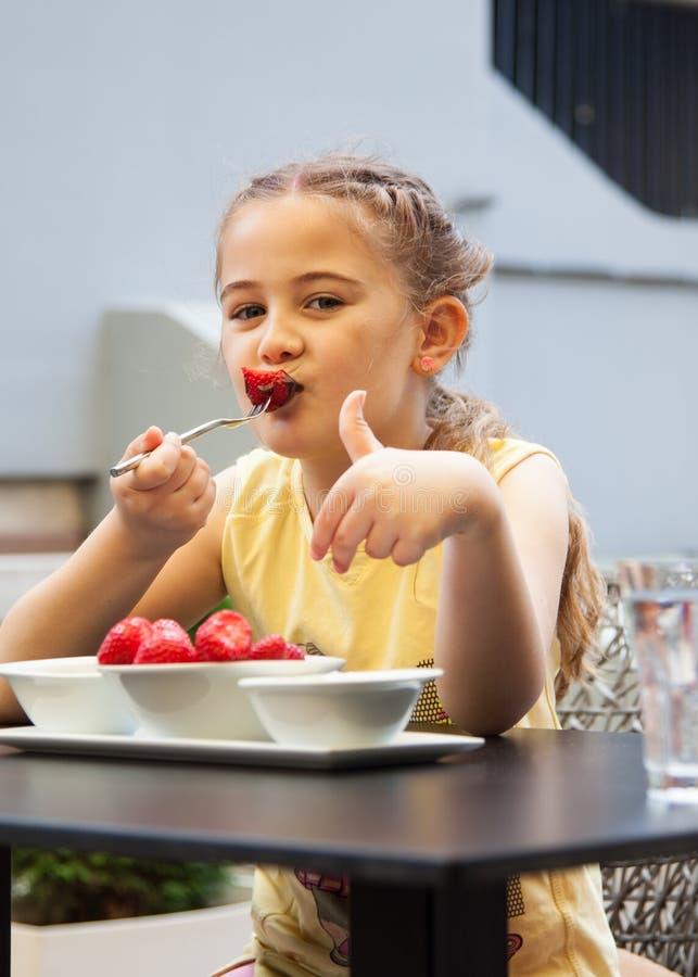 Het gelukkige kindmeisje eet aardbeien in de zomer, Jonge leuke smil royalty-vrije stock afbeelding
