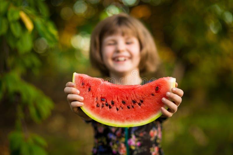 Het gelukkige kindmeisje eet watermeloen in de zomer stock afbeeldingen