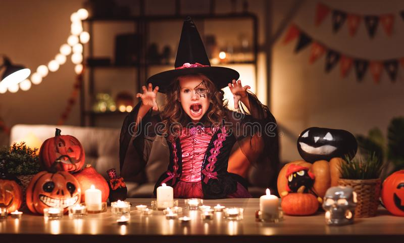 Het gelukkige kindmeisje in kostuums van heks in een donker huis zegent binnen royalty-vrije stock foto