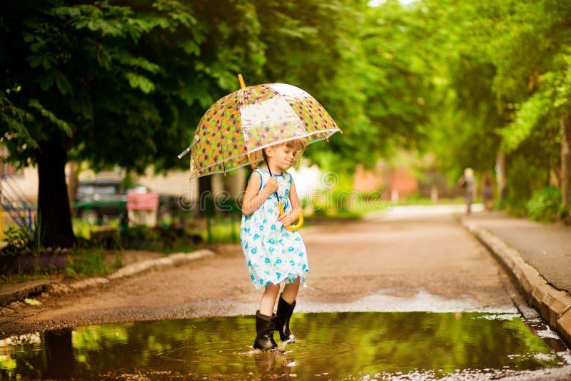 Het gelukkige kindmeisje met een paraplu en de rubberlaarzen in vulklei op de zomer lopen royalty-vrije stock fotografie