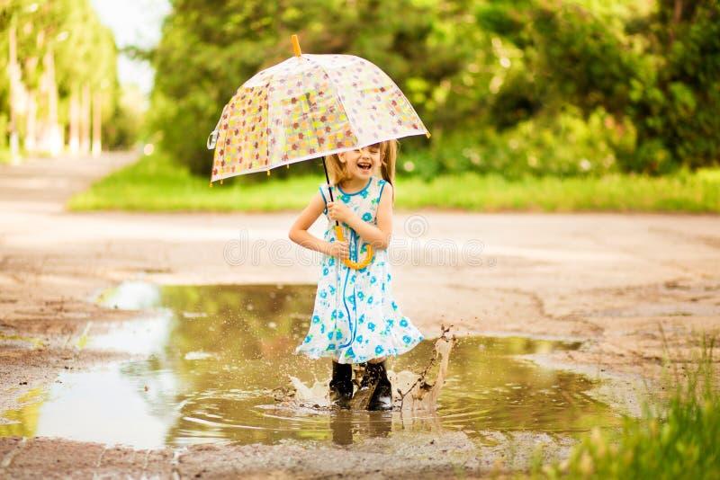 Het gelukkige kindmeisje met een paraplu en de rubberlaarzen in vulklei op de zomer lopen stock foto's