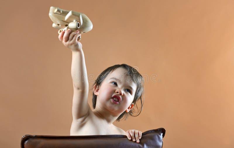 Het gelukkige kindmeisje spelen met stuk speelgoed vliegtuig royalty-vrije stock afbeelding