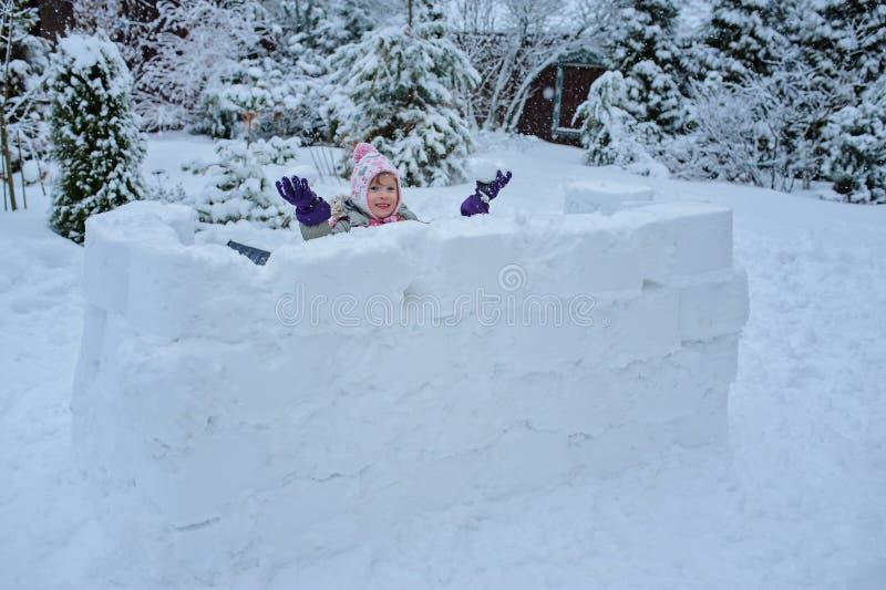 Het gelukkige kindmeisje spelen in sneeuwkasteel in het dalen doet escaleren op de winterbinnenplaats stock afbeeldingen