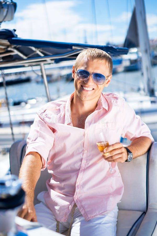 Het gelukkige knappe mens ontspannen op een boot royalty-vrije stock afbeelding