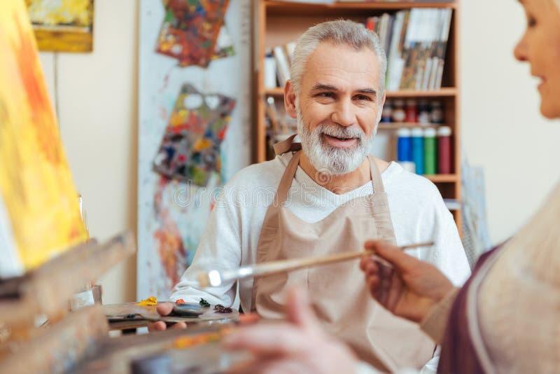 Het gelukkige kunstenaar schilderen in klasse stock afbeeldingen